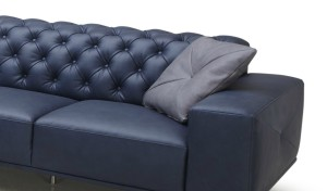 blue leather sofa with tufted back and gray cushion