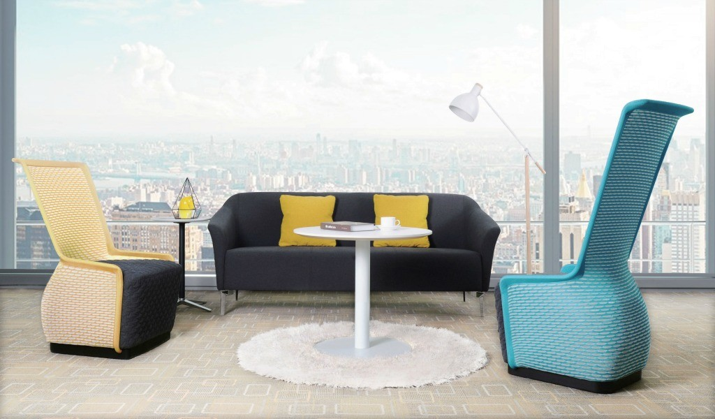 Lounge area with sofa, coffee table and lounge chairs in colorful fabric