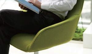 a person sitting in an easy chair upholstered in green fabric