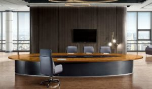 large boardroom with oval shape conference table and chairs
