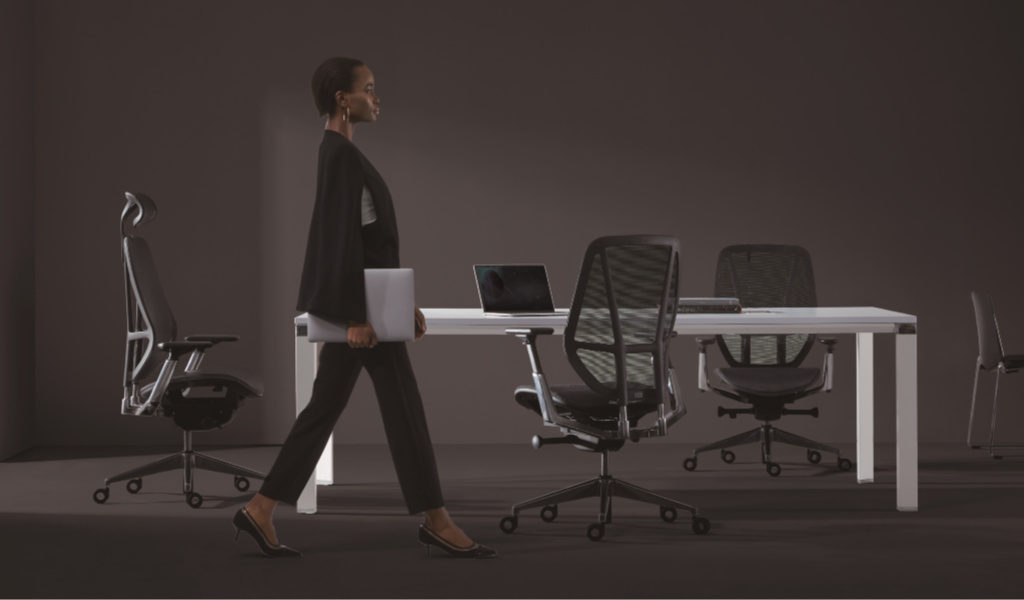 modern conference room with ergonomic chairs and a person walking by
